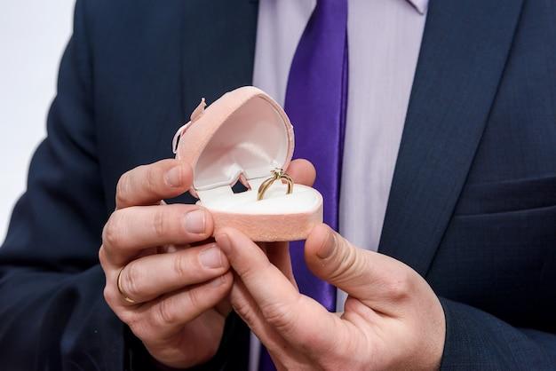 Le marié donne la bague de mariage dans une boîte rouge