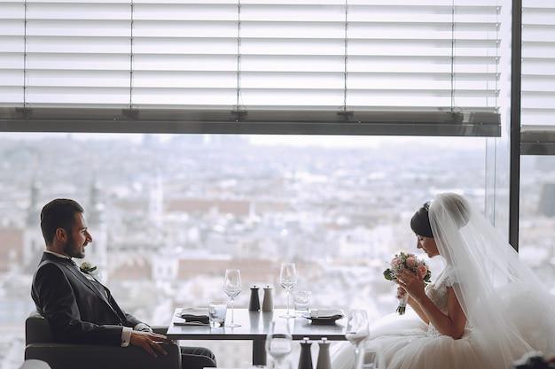 Le marié élégant et élégant et sa jolie femme assise dans un restaurant