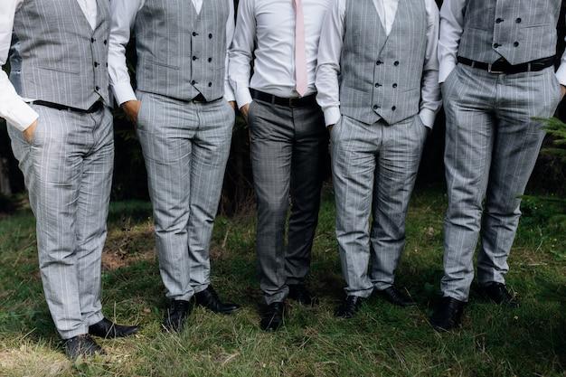 Le marié élégant et ses garçons d'honneur se tiennent sur l'herbe