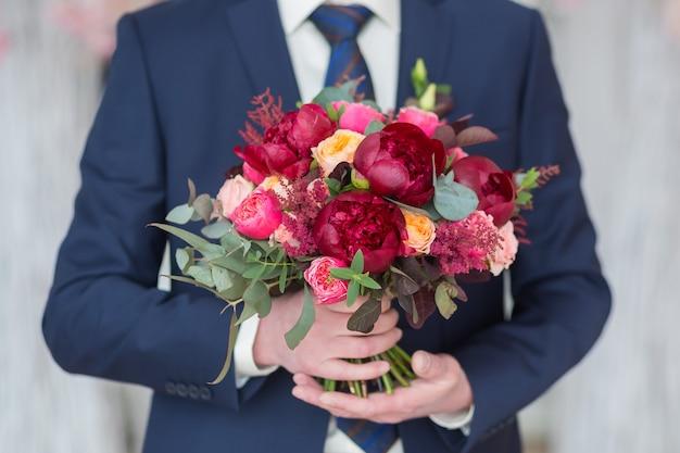 Marié élégant tenant un bouquet de mariage