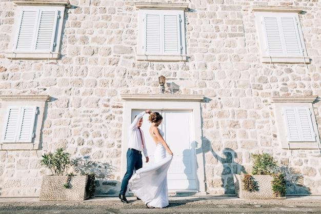 Le marié a élevé la main en marchant le long de la rue devant un vieux bâtiment avec des stores aux fenêtres