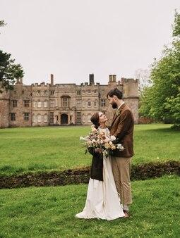 Marié embrassant regarde la mariée sur le fond d'un champ de temps nuageux
