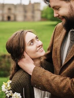 Marié embrassant regarde la mariée sur le fond du champ, campagne, pelouse verte