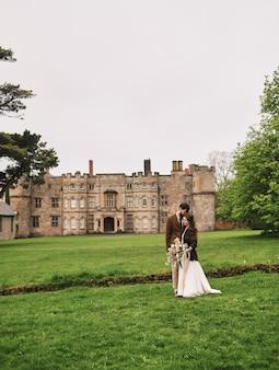 Marié embrassant regarde la mariée sur le fond du champ
