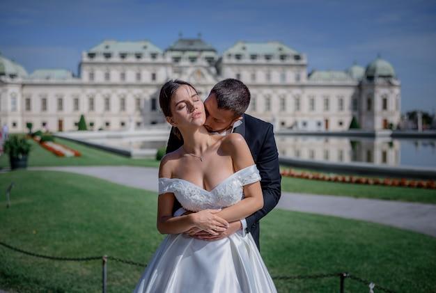 Le marié embrasse le cou de la mariée devant l'immense palais résidentiel du roi