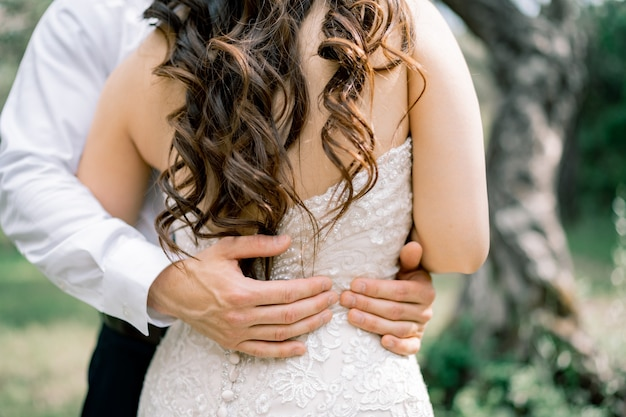 Le marié embrasse doucement les mains de la mariée du marié sur la taille de la mariée en gros plan