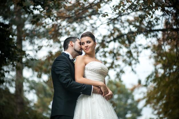 Le marié embrasse doucement la mariée avec un bouquet par derrière dans un parc