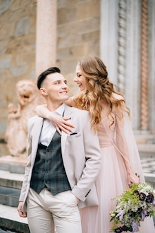 Le marié embrasse et embrasse la mariée à l'entrée de la basilique de santa maria
