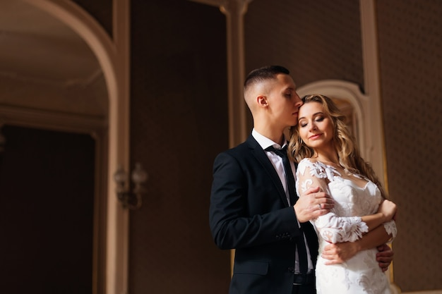 Le marié embrasse et embrasse la mariée. jeunes mariés. fermer.