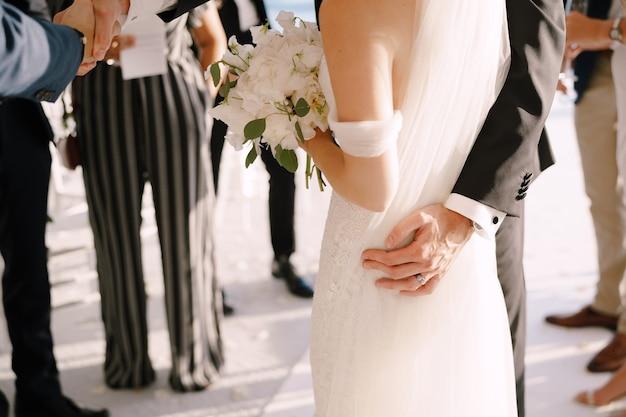 Le marié embrasse la mariée avec un bouquet tout en se tenant devant les invités