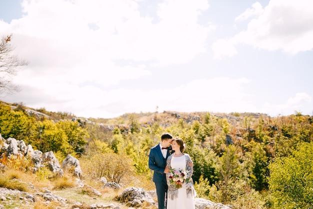 Le marié embrasse la mariée dans un châle à carreaux avec un bouquet