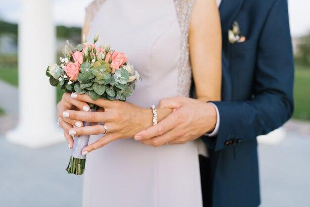 Le marié embrasse la mariée, une grande vue des mains. la mariée tient un délicat bouquet de fleurs dans ses mains