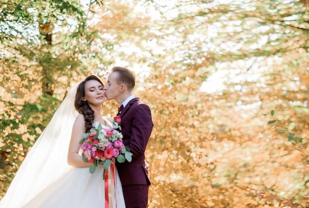 Le marié embrasse la mariée sur la joue entourée d'arbres d'automne jaunes