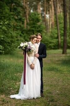 Le marié embrasse la mariée par derrière dans la forêt