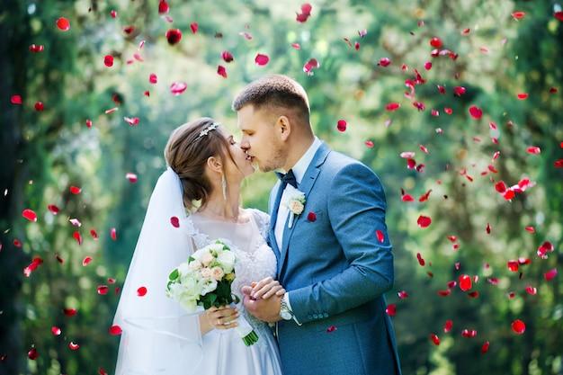 Le marié embrasse la mariée en pétales de rose