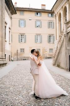 Marié embrasse la mariée en se tenant debout sur les pavés près de l'ancien bâtiment à bergame italie