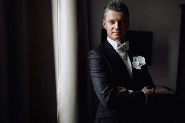 Le marié est le matin. bel homme en smoking noir avec orchidée blanche