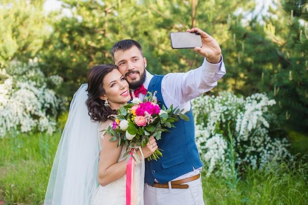 Le marié fait une photo avec sa mariée à l'extérieur