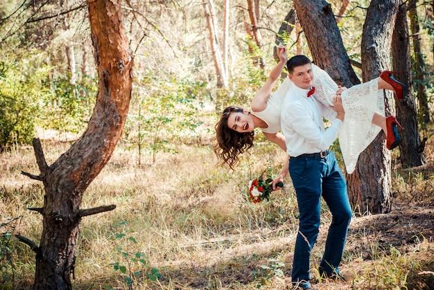 Marié fuyant avec mariée sur son dos à l'extérieur dans l'allée du parc