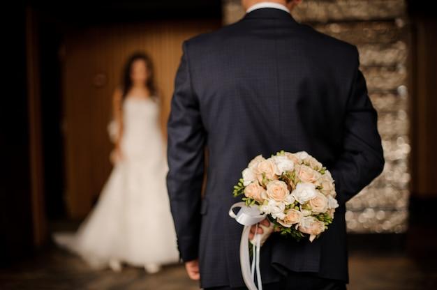 Marié, garder, derrière, a, bouquet roses, attente, mariée