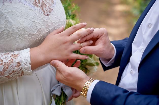 Le marié habille la bague de la mariée à son doigt