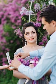 Le marié habille la mariée avec des alliances près de l'arc lilas