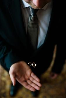 Marié heureux avec les alliances en or sur sa main. jour de mariage