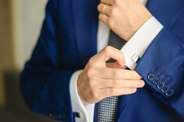 Le marié ou l'homme d'affaires attache le bouton de manchette sur le poignet de la chemise portant un costume bleu