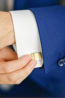 Le marié ou l'homme d'affaires attachent le bouton de manchette