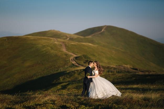 Marié et mariée sur la colline dans les montagnes. couple de mariage en face de la colline verte.