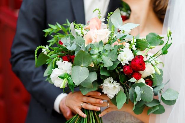 Marié et mariée élégante dans une robe de mariée avec dentelle et voile tenant un bouquet de fleurs de mariée