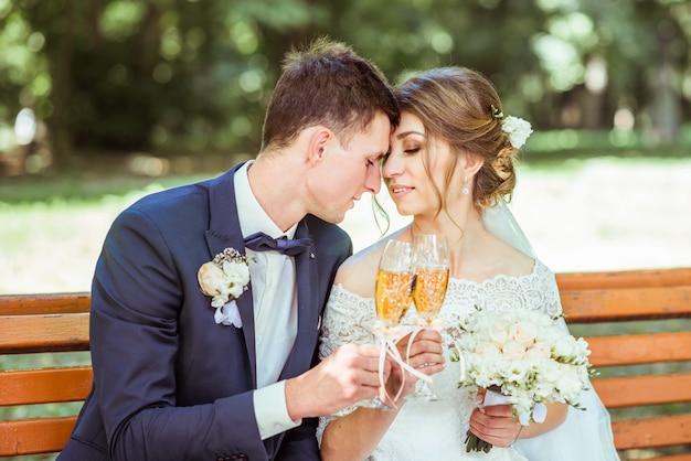 Le marié et la mariée est assis dans le parc