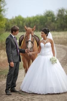 Le marié et la mariée lors d'une promenade le jour de leur mariage contre un cheval brun