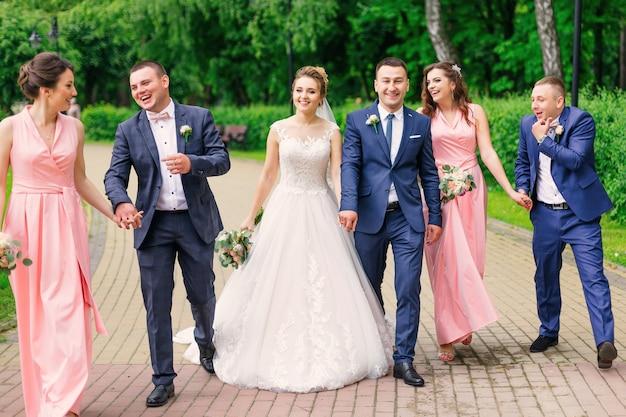 Le marié et la mariée marchent avec le garçon d'honneur et la demoiselle d'honneur dans le parc.