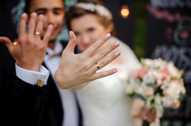 Le marié et la mariée montrant des anneaux de mariage sur leurs doigts