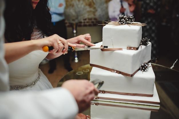Marié et mariée prêts à couper le gâteau de mariage