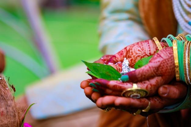 Le marié et la mariée tenant la feuille verte et la sculpture du seigneur ganesha à la main