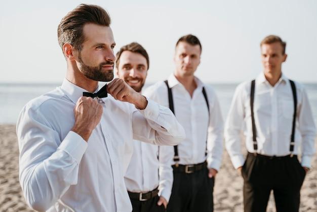 Marié et meilleurs hommes posant sur la plage