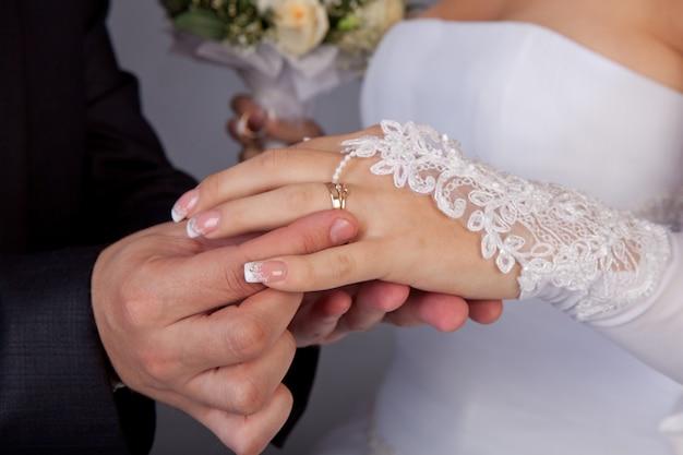 Le marié met sur un anneau une main à la mariée
