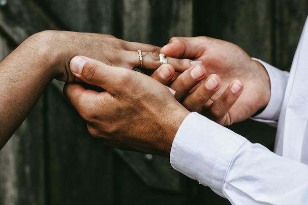 Le marié met la bague sur le bras de sa fiancée
