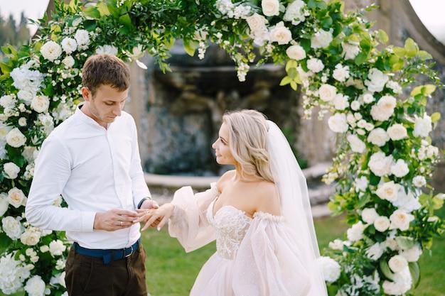 Le marié met une bague sur le doigt de la mariée