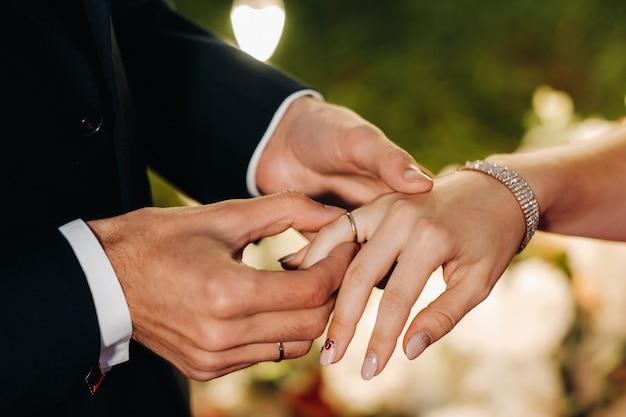 Le marié met une bague de fiançailles au doigt de la mariée le jour de leur mariage