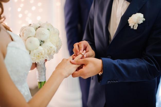 Le marié met une bague de mariage au doigt d'une belle mariée