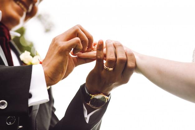 Le marié met la bague de mariage au doigt de la mariée