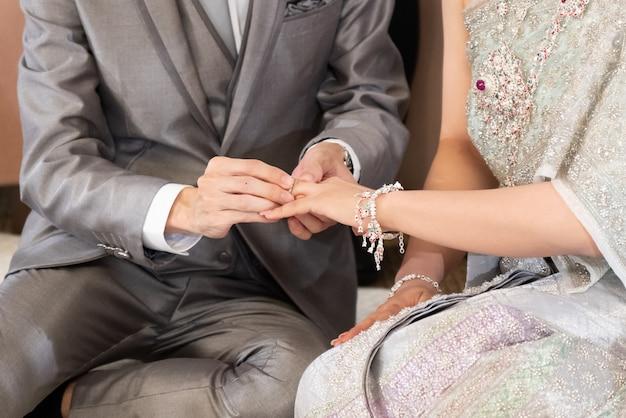 Le marié met une bague de mariage dans un doigt de la mariée inthai wedding concept