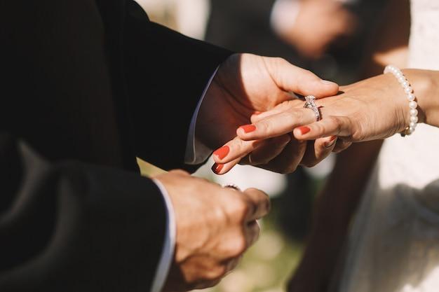 Marié met une bague de mariage sur le doigt de la mariée en le tenant tendre