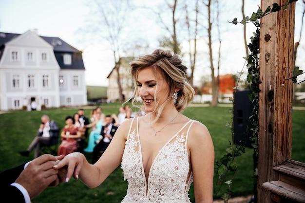 Le marié met la bague de mariage sur le doigt de la mariée