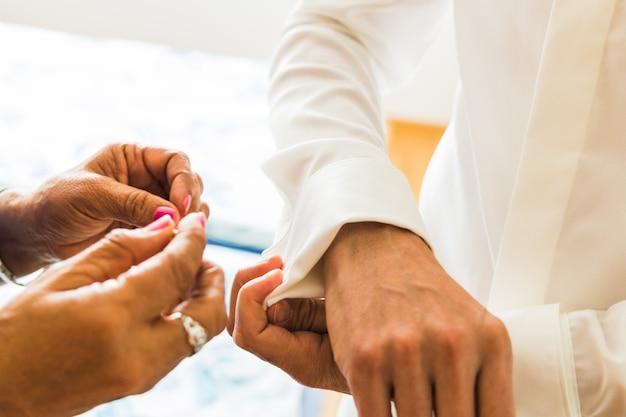 Un marié met des boutons de manchette alors qu'il s'habille le jour de son mariage. costume du marié