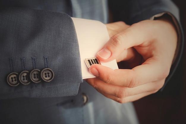 Le marié met des boutons de manchette à mesure qu'il s'habille de façon formelle