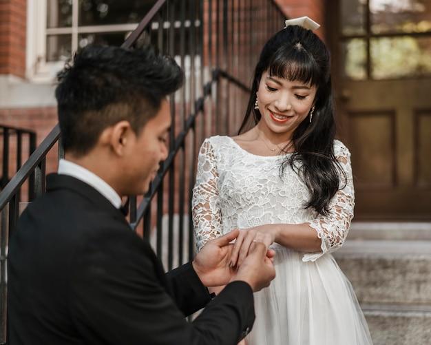 Marié mettant la bague de mariage sur le doigt de la mariée